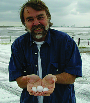 Achtor holding hail stones while storm chasing in 2002.